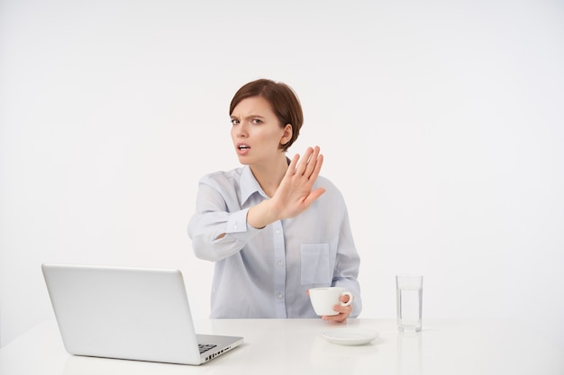 Jovem morena de cabelos curtos descontente com maquiagem natural, franzindo a testa e levantando a mão em sinal de recusa enquanto se senta à mesa no interior do escritório