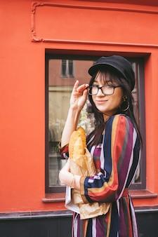 Jovem morena de cabelos longos em um vestido brilhante contra uma parede vermelha com baguetes de pão em um saco de papel
