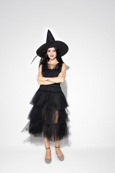 Jovem morena de chapéu preto e fantasia branca