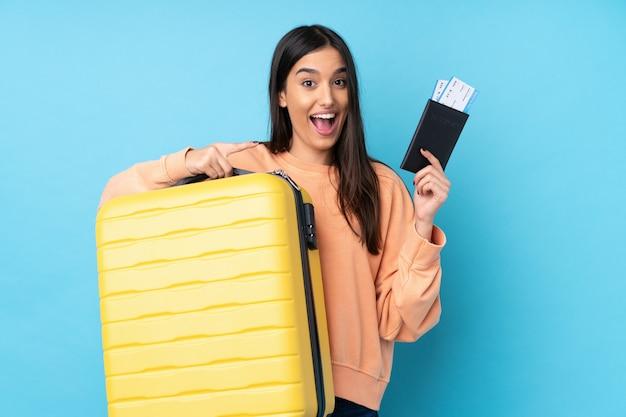Jovem morena de férias com mala e passaporte e surpresa