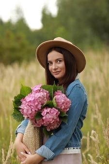 Jovem morena de jaqueta jeans e chapéu está segurando um buquê de saco de palha de hortênsia de flores cor de rosa, enquanto caminha ao ar livre pelo campo no verão.