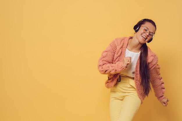 Jovem morena de óculos e fones de ouvido vestida de blusa de camisola rosa branca e calça amarela, cantando e dançando satisfeito por seu estilo de vida, sobre fundo amarelo. positivo e jovem. hora da festa.