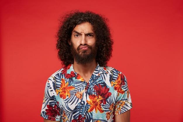 Jovem morena de olhos castanhos com cabelo encaracolado fazendo careta e franzindo a testa, usando uma barba exuberante e uma camisa florida multicolorida