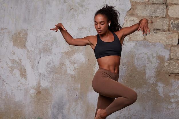 Jovem morena de pele escura e cacheada, com top preto e leggins bege, preparando uma dança moderna enquanto posa sobre uma parede de tijolos