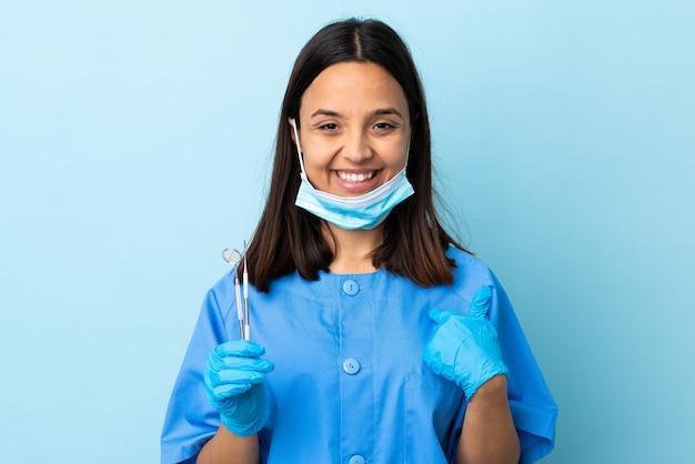 Jovem morena de raça mista dentista segurando ferramentas na parede isolada com expressão facial surpresa