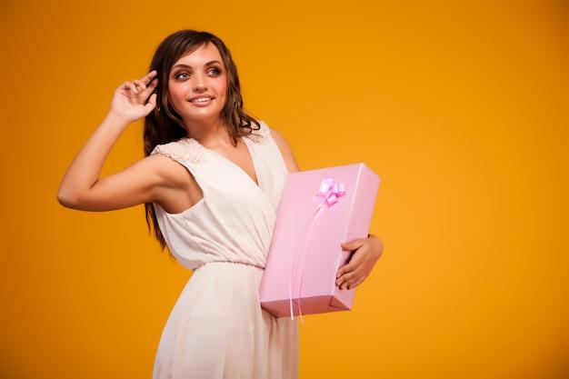 Jovem morena de vestido bege em pé, segurando a caixa de presente rosa nas mãos e sorrindo sobre amarelo escuro