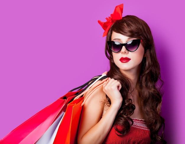 Jovem morena de vestido vermelho com sacolas de compras roxas