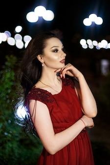 Jovem morena de vestido vermelho com um trem posando em um parque noturno