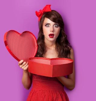 Jovem morena de vestido vermelho e laço com caixa git roxa