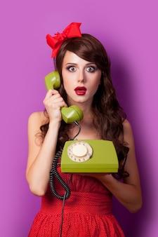 Jovem morena de vestido vermelho e laço com telefone fixo verde segurando o monofone roxo