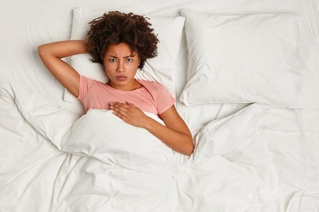 Jovem morena deitada na cama
