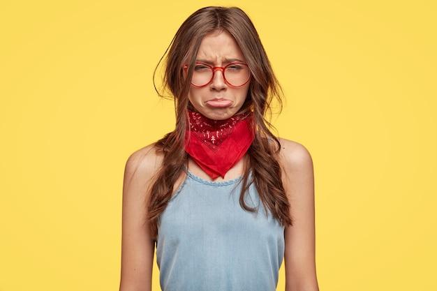 Jovem morena deprimida com óculos posando contra a parede amarela