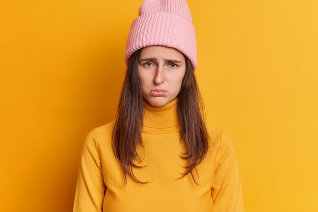 Jovem morena descontente com expressão ofendida olhar amuado expressa emoções negativas usa chapéu e blusão casual.
