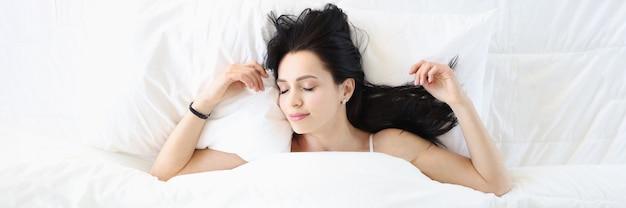 Jovem morena dormindo em uma cama branca, vista de cima, conceito de sono saudável