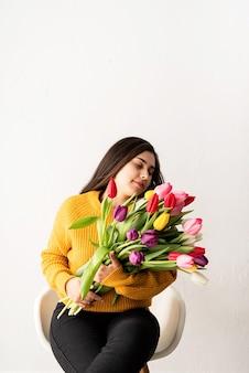 Jovem morena em mulher de suéter amarelo com buquê de tulipas cor de rosa frescas