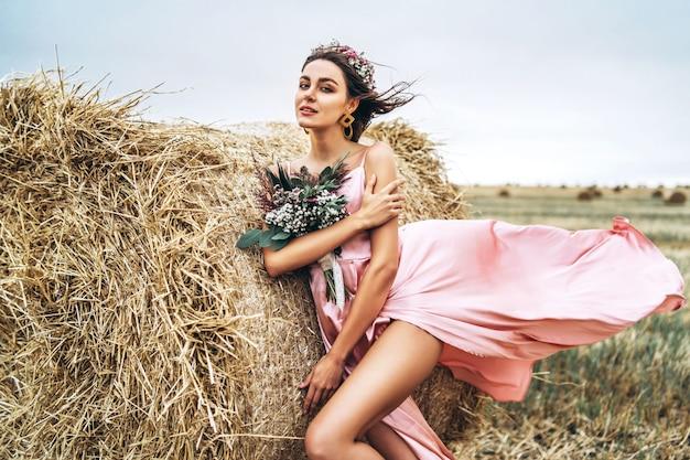 Jovem morena em um vestido de cetim rosa, sem roupa de pé perto de fardos de feno em tempo ventoso. uma mulher segura um buquê de flores silvestres