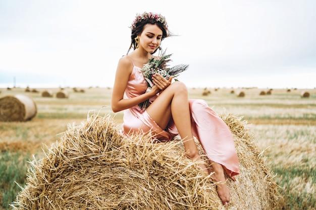 Jovem morena em um vestido de cetim rosa, sentado em um fardo de feno. uma mulher tem uma coroa na cabeça e segura um buquê de flores silvestres nas mãos