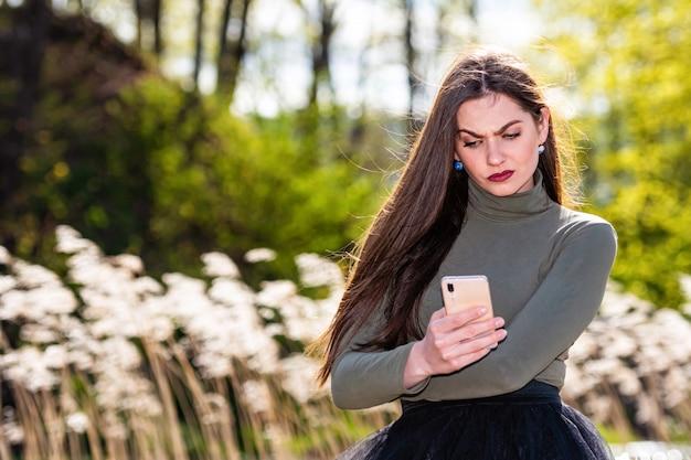 Jovem morena emocional bonita se sentir triste quando ela leu a mensagem no smartphone
