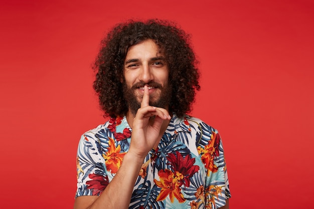 Jovem morena encaracolada alegre com barba levantando o dedo indicador em gesto silencioso, olhando positivamente para a câmera com um sorriso agradável, isolado sobre um fundo vermelho em roupas casuais