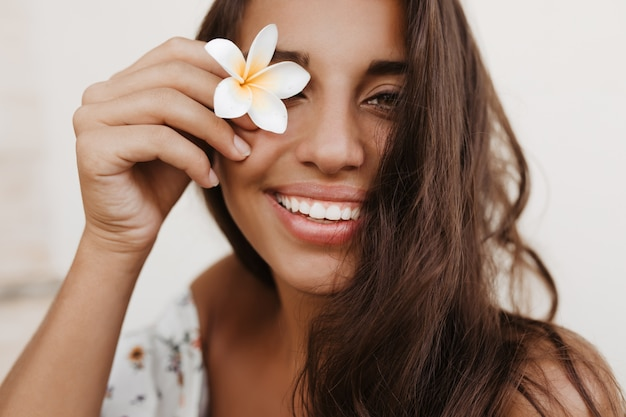 Jovem morena encaracolada cobrindo os olhos com uma flor branca