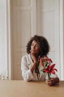 Jovem morena encaracolada séria, de pele escura, com blusa branca desvia o olhar, inclina-se sobre a mesa de madeira e segura um vaso com flores vermelhas