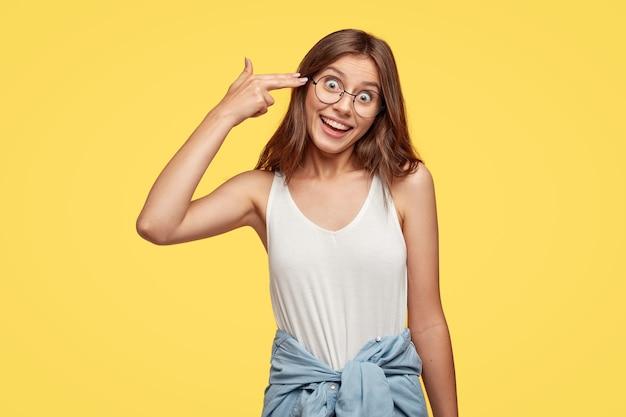 Jovem morena engraçada com óculos posando contra a parede amarela
