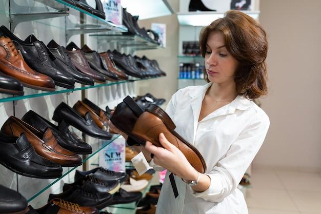 Jovem morena escolhe entre dois pares de sapatos masculinos de cores diferentes na loja de sapatos