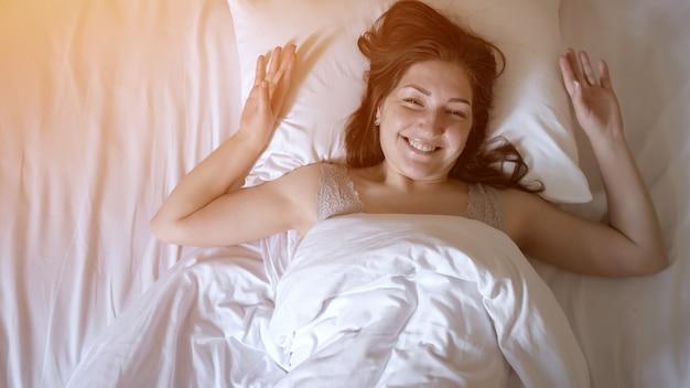 Jovem morena está acordando na cama com linho branco. ela está permanecendo em sua cama cochilando de manhã nas férias, vista de cima