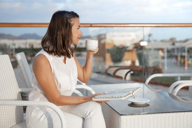 Jovem morena está curtindo a manhã com um copo de bebida quente e um livro nas mãos. conceito de descanso e relaxamento.