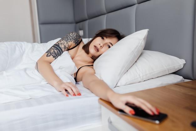 Jovem morena está tomando o telefone tocando da mesa de cabeceira perto de sua cama de manhã