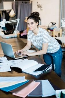 Jovem morena estilosa em trajes casuais, curvando-se sobre a mesa e o laptop enquanto percorre coisas online