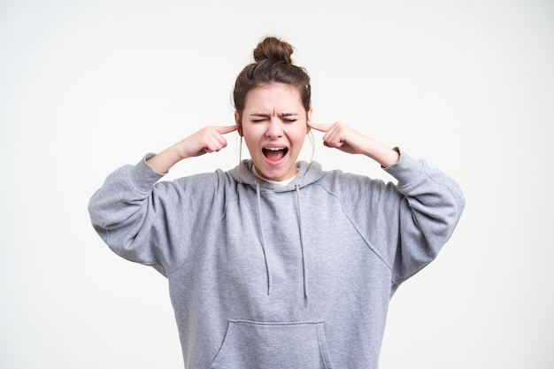 Jovem morena estressada com penteado coque, gritando com os olhos fechados e colocando os dedos indicadores nas orelhas, em pé sobre um fundo branco em uma roupa esportiva