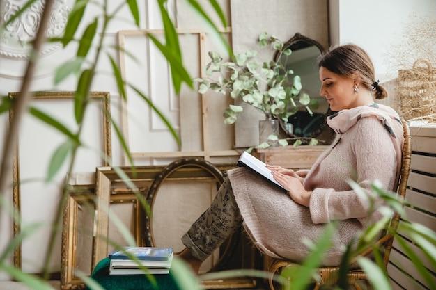 Jovem morena europeia em um casaco de lã bege quente sentada em uma cadeira de vime
