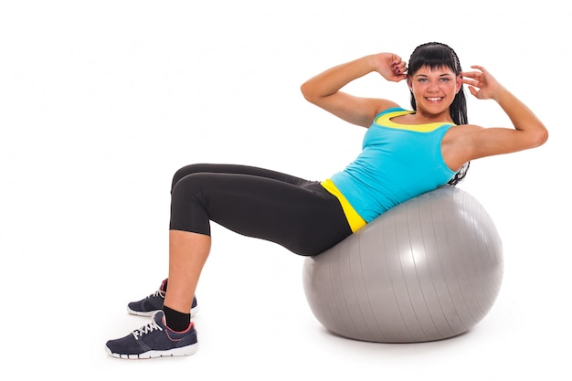Jovem morena feliz exercitando com fitball