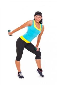 Jovem morena feliz exercitando com halteres