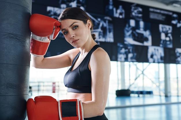 Jovem morena feminina com roupas esportivas e luvas de boxe, olhando para você enquanto treina com um saco de pancadas na academia