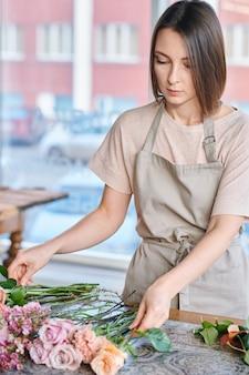 Jovem morena feminina em roupas de trabalho, classificando rosas frescas e outras flores pelo local de trabalho na loja