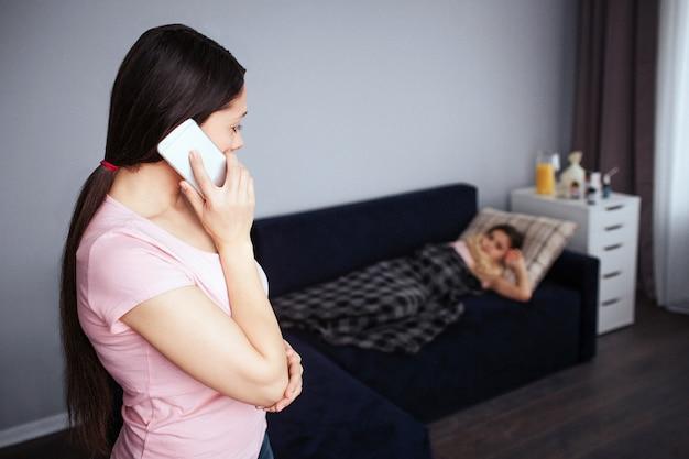 Jovem morena ficar na sala e falar no telefone. ela olha para a filha doente. menina deitada no sofá. ela cobriu com o cobertor.