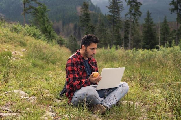 Jovem morena homem de jeans e camisa está trabalhando em um computador enquanto estiver na natureza. o conceito de trabalho como freelancer.