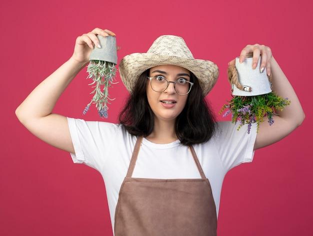 Jovem morena impressionada com óculos e uniforme, usando um chapéu de jardinagem segurando vasos de flores de cabeça para baixo isolados na parede rosa com espaço de cópia