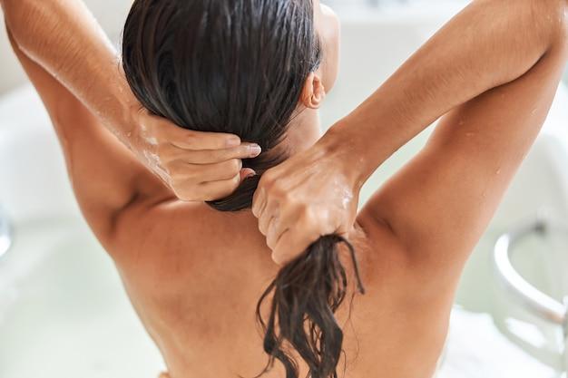 Jovem morena lavando cabelo no banheiro