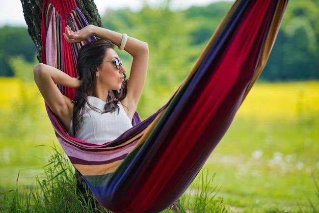 Jovem morena linda em óculos de sol é encontra-se numa rede no contexto do campo. fechar-se.