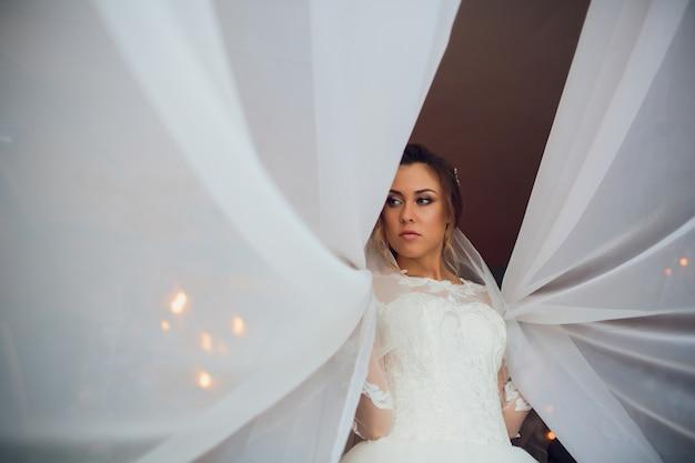 Jovem morena linda no vestido de casamento.