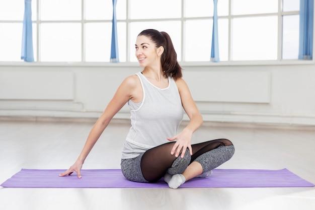 Jovem morena linda pratica ioga no corredor.