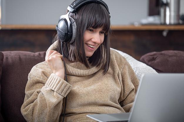 Jovem morena linda sorrindo com um suéter aconchegante e olhando para a tela do laptop.