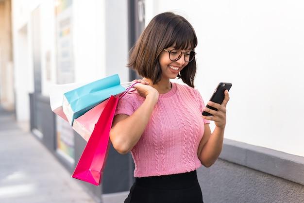 Jovem morena na cidade segurando sacolas de compras e escrevendo uma mensagem com seu celular para uma amiga
