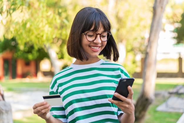 Jovem morena no parque comprando com o celular com cartão de crédito