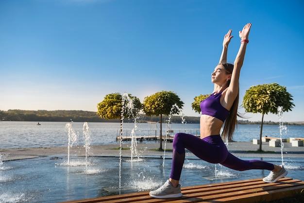 Jovem morena no sportswear fazendo alongamento das pernas após o treino no lago perto do dia. estilo de vida saudável