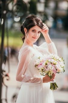 Jovem morena noiva em um vestido branco com buquê. closeup retrato de uma mulher ao ar livre