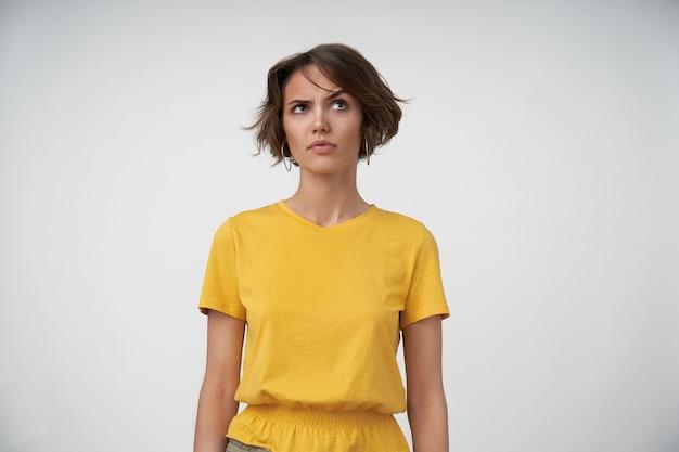 Jovem morena perplexa com penteado casual, vestindo uma camiseta amarela, posando com as mãos para baixo, olhando para cima com uma sobrancelha levantada